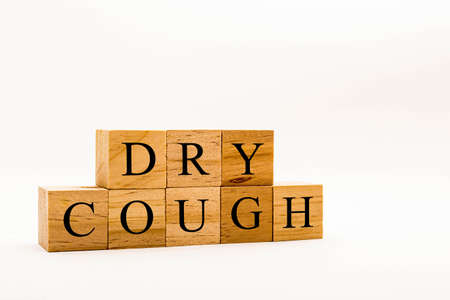 Coronavirus concept showing wooden blocks on a white background reading Dry Cough