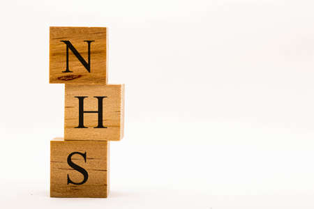 Coronavirus concept showing wooden blocks on a white background reading NHS