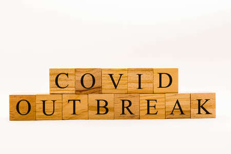 Coronavirus concept showing wooden blocks on a white background reading Covid Outbreak Banque d'images