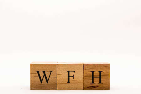Coronavirus concept showing wooden blocks on a white background reading WFH