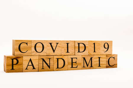 Coronavirus concept showing wooden blocks on a white background reading Covid19 Pandemic Archivio Fotografico