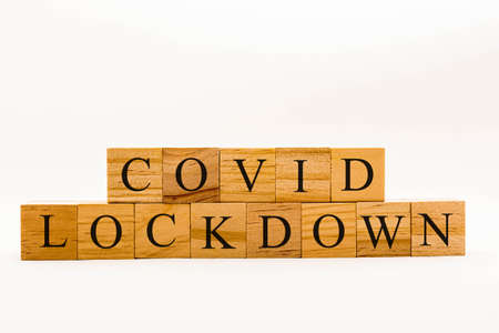 Coronavirus concept showing wooden blocks on a white background reading Covid Lockdown Banque d'images