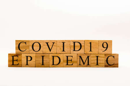 Coronavirus concept showing wooden blocks on a white background reading Coviid19 Epidemic