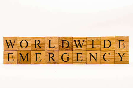 Coronavirus concept showing wooden blocks on a white background reading Worldwide Emergency