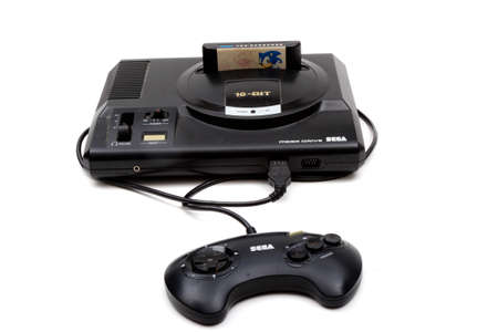 London, United Kingdom, 21st September 2020:- A retro Sega Mega Drive 16-bit gaming console with controller and Sonic The Hedgehog game isolated on a white background Editorial
