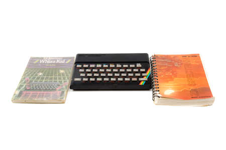 London, United Kingdom, 21st September 2020:- A retro Sinclair ZX Spectrum 48k home computer with books isolated on a white background
