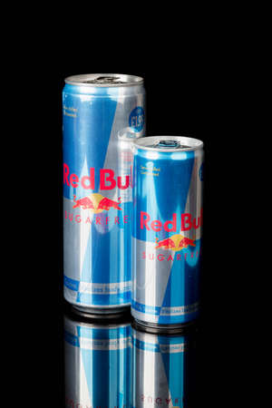 London, United Kingdom, 14th October 2020:- Large & Small Cans of Red Bull Sugar Free Energy Drink Isolated on a black background