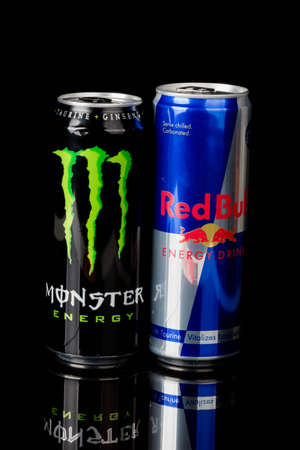 London, United Kingdom, 14th October 2020:- Cans of Monster and Redbull Energy Drinks Isolated on a black background