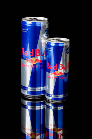 London, United Kingdom, 14th October 2020:- Cans of large and Small Red Bull Energy Drinks Isolated on a black background Redakční