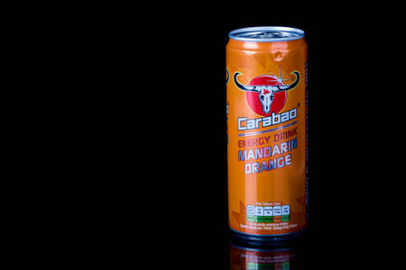 London, United Kingdom, 14th October 2020:- A can of Carabao Mandarin Orange Energy Drink Isolated on a black background Redakční