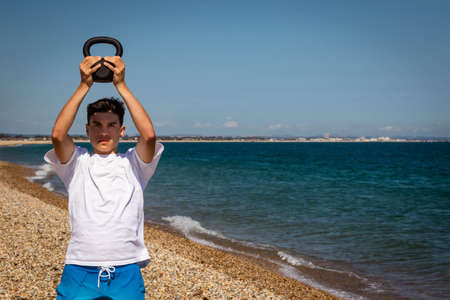 A 18 year old Caucasian shirtless teenage boy on a beach exercising with a kettlebell weight using both hands with copy space Stock Photo