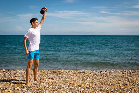 A 18 year old Caucasian teenage boy on a beach exercising with a kettlebell weight