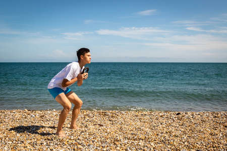 A 18 year old Caucasian teenage boy on a beach exercising with a kettlebell weight with copy space Stock Photo