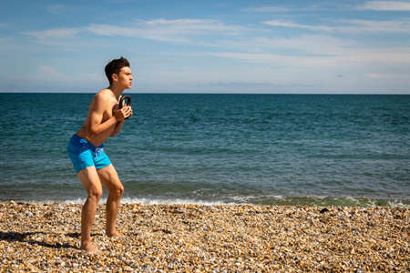 A 18 year old Caucasian shirtless teenage boy on a beach exercising with a kettlebell weight with copy space Stock Photo
