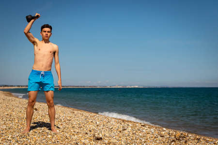 A 18 year old Caucasian shirtless teenage boy in swimwear exercising with a kettlebell weight with copy space