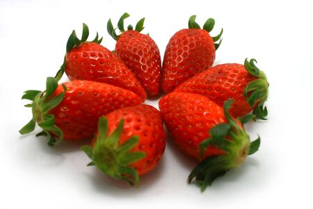Steven brightly red strawberries on a white background form up a pattern.