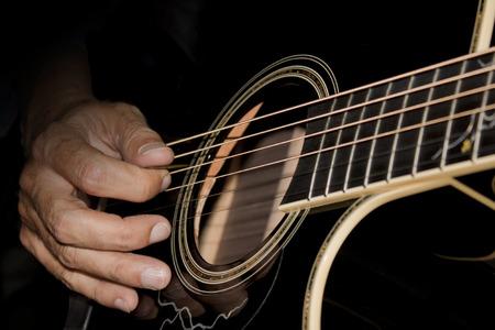 黒のアコースティック ギターを演奏する男のクローズ アップ