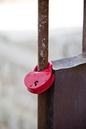ハート形の非常に錆ついているフェンスに南京錠