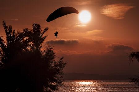 男がビーチで日の出背景にパラグライダーの練習
