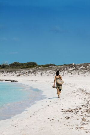 young lonely woman walking on the beach