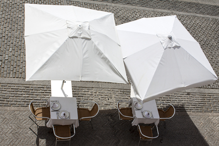 summer terrace with tables and white umbrellas