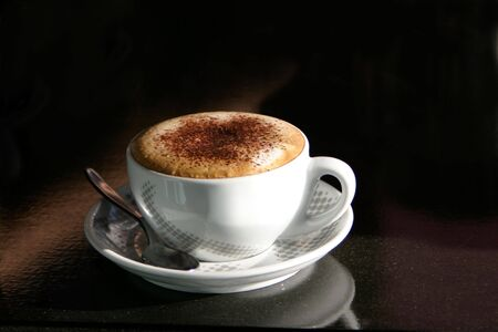 Cappuccino served in a ceramic cup against a dark background