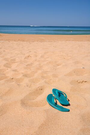 A pair of green flip-flops sitting in the sand at the beach