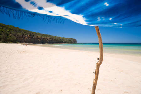 A view of a perfect beach scene from under the shade of a sarong