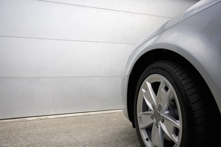 A silver car sits in front of a garage Stock Photo