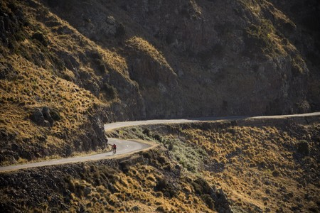 A cyclist on a winding road Stock Photo
