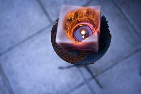 A rustic old candle is lit at a function venue