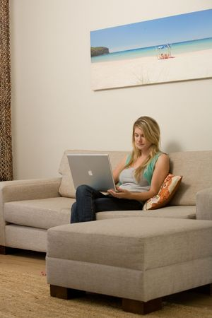 A blond Caucasian woman sits with a laptop computer in a modern residential setting