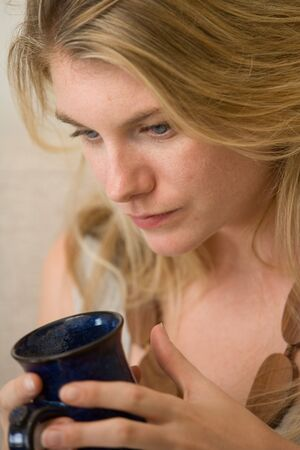 A young woman with a worried expression holds a blue mug close to her face