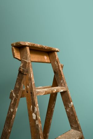 An old rustic ladder standing against a green wall