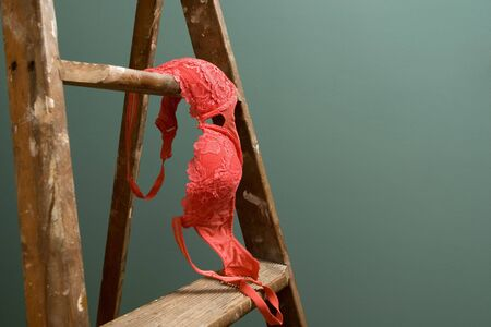 A bright pink bra sits on an old rustic ladder standing against a green wall Stock Photo