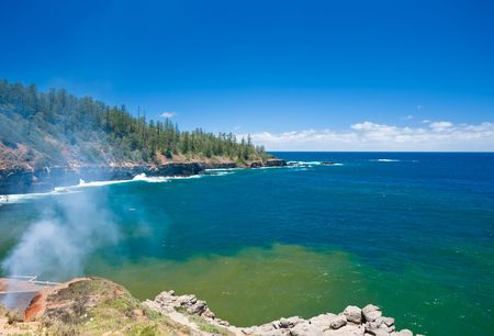 effluent: Smoke rises into the air and effluent fills stains the water on the coast Stock Photo