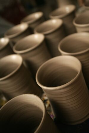 Three rows of brown newly created pottery mugs