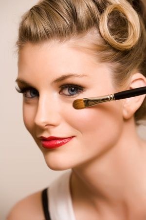 A young white woman has makeup applied to her face