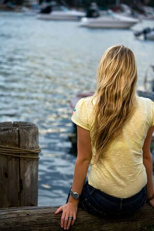 A girl sits at a wharf overlooking the water