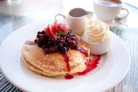 Pancake stack with berries, fresh cream and maple syrup