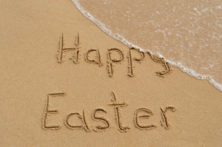 Happy Easter written written in the sand at the beach and washed away by waves