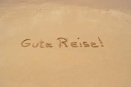 translated: The German phrase Gute Reise (translated: Have a good trip) written in the sand at the beach Stock Photo