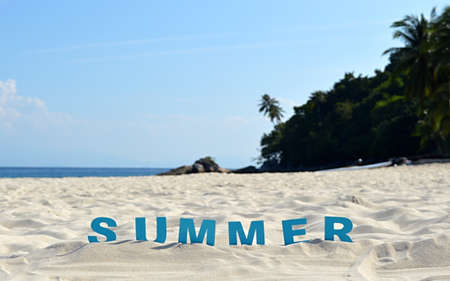 spelled: The word summer spelled out with blue letters in the sand at a tropical beach Stock Photo