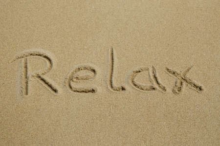 The word relax written in the sand at the beach Stock Photo
