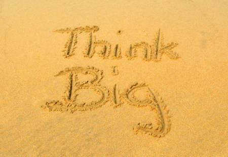 think big: The message think BIG in the sand Stock Photo