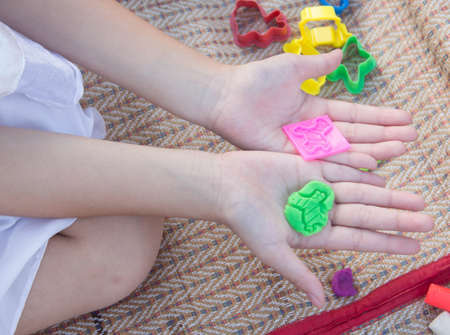 plasticine: Plasticine toy in hand girl. Stock Photo