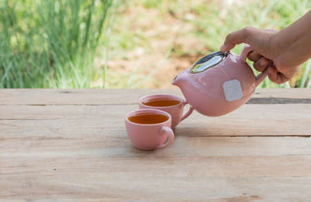 trivet: Hand pouring tea on a wooden table.