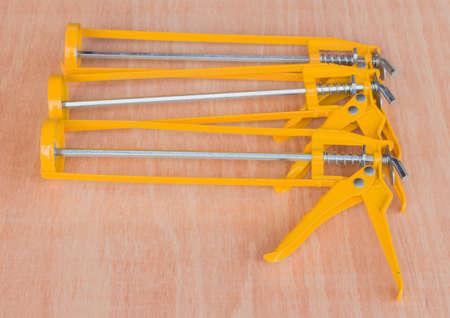 silicio: amarilla pistola de pegamento de silicona en un piso de madera. Foto de archivo