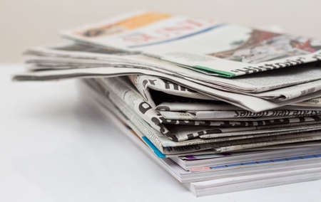 newspaper: Magazines and newspapers on white table.