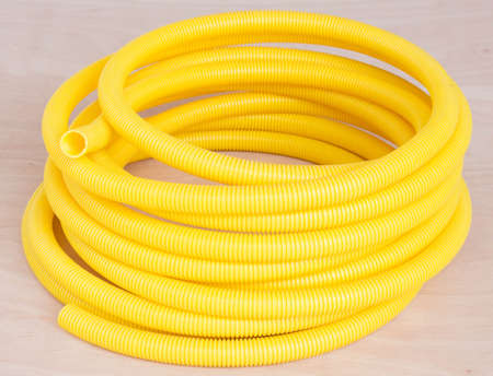 plastic conduit: Plastic corrugated pipe color yellow on the wooden floor.